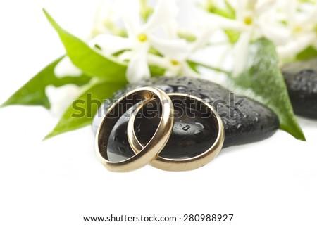 wedding rings of yellow gold with white jasmine flowers - stock photo