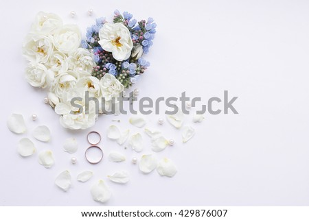 wedding rings on a background of rose petals - stock photo