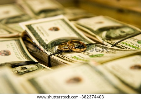 wedding rings on a pack of dollars - stock photo