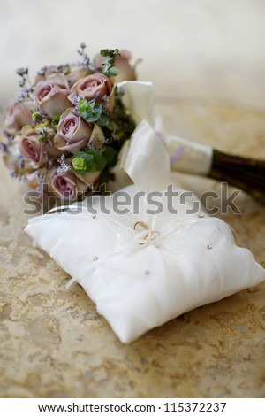 Wedding rings on a pillow and a bouquet - stock photo