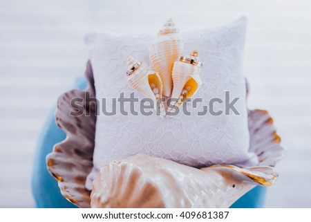Wedding rings on a pillow with seashells, stylized wedding - stock photo