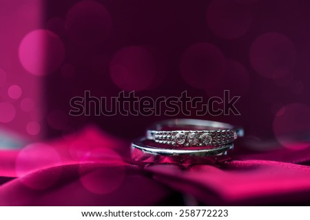 Wedding rings on a pink background. - stock photo