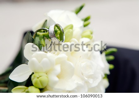 Wedding rings on a white flowers, focused to the rings - stock photo