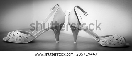 Wedding rings on bride's shoes - stock photo