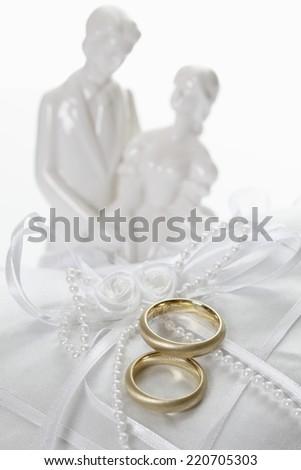 Wedding rings on cushion with couple figurine - stock photo