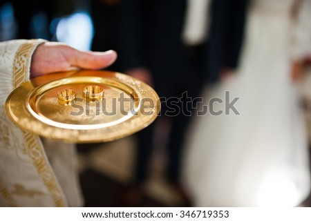 wedding rings on discus at hand of priest - stock photo