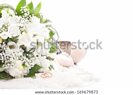 Wedding rings on lace against wedding bouquet and shoes - stock photo