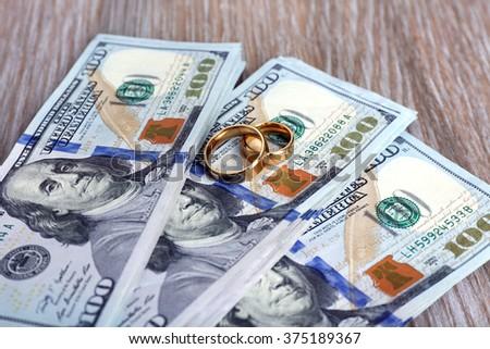 Wedding rings on money background, close up - stock photo