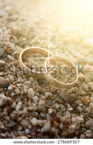 Wedding rings on sea sand. wedding rings close up - stock photo