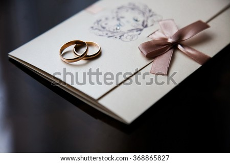 Wedding rings on the invitation card, rings on a dark background, preparations for the wedding, wedding decorations  - stock photo