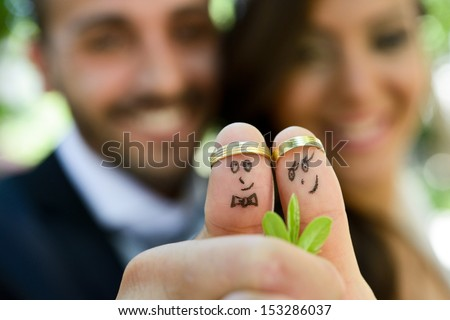 wedding rings on their fingers painted with the bride and groom, funny little people  - stock photo
