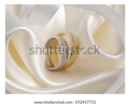 Wedding rings on white silk - stock photo