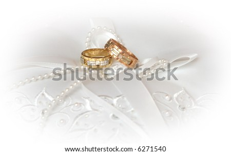 Wedding Rings on white silk and pearl - stock photo