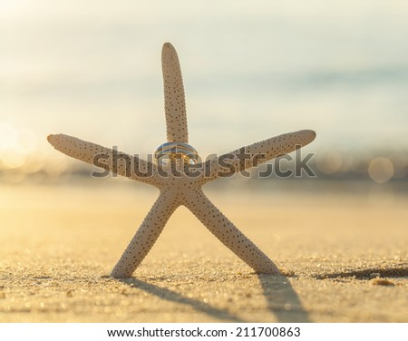 Wedding rings put on the beach side. - stock photo