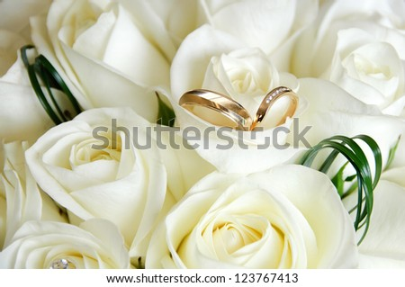 Wedding rings resting on white roses at a wedding - stock photo