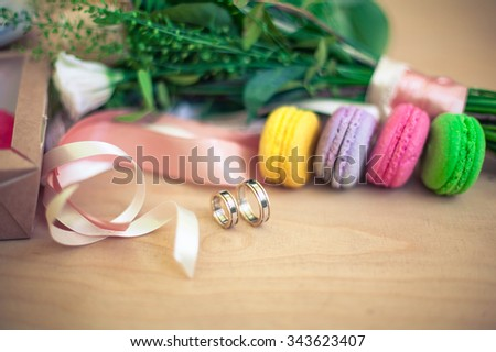 wedding rings with bouquet and macaroons - stock photo