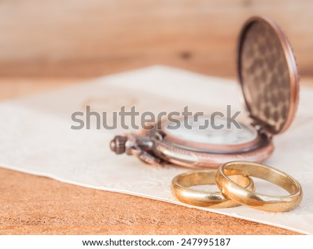 Wedding rings with pocket watch background for wedding or valentines days concept. - stock photo