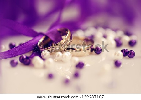 wedding rings with purple ribbon, perls, diamonds in yellow gold, wedding day, love - stock photo
