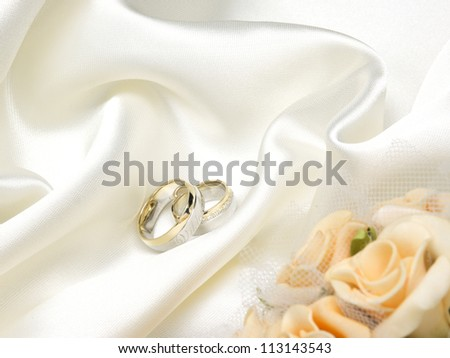 Wedding rings, yellow roses and white silk - stock photo