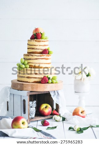 Wedding rustic cake with flowers and fruits - stock photo