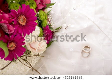 Wedding setting - top view of bride and groom rings and beautiful colourful bouquet of flowers on white wedding gown. - stock photo