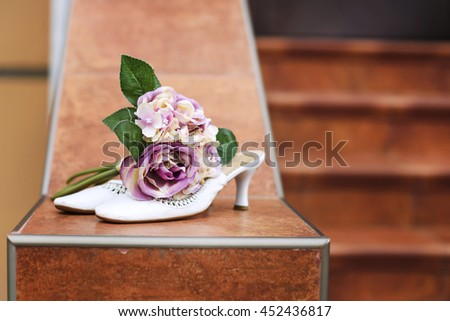 wedding shoes and wedding bouquet in the grass - stock photo