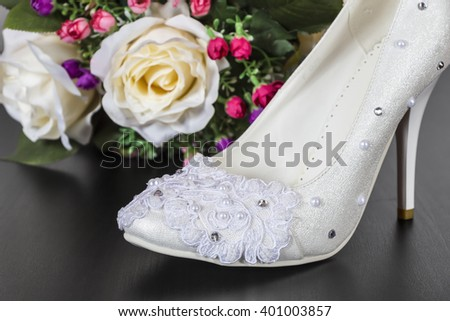 Wedding shoes are standing on the table against the background of a bouquet of roses - stock photo