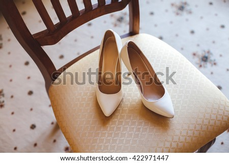 Wedding shoes cream color on the chair at the hotel.
