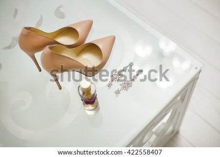 Wedding shoes cream-coloured white on a glass table. Spirits. Earrings.