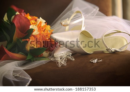 Wedding shoes with veil and rings on chair - stock photo
