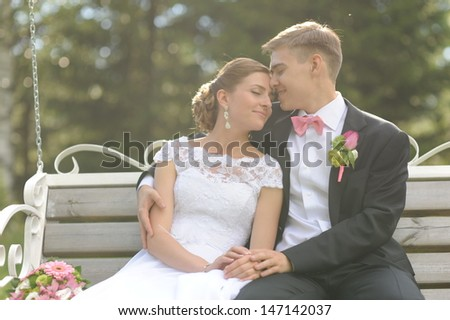 Wedding shot of bride and groom sit on bench in park - stock photo