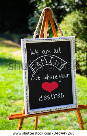 Wedding sign for seating arrangements says we are all family sit where your heart desires. - stock photo