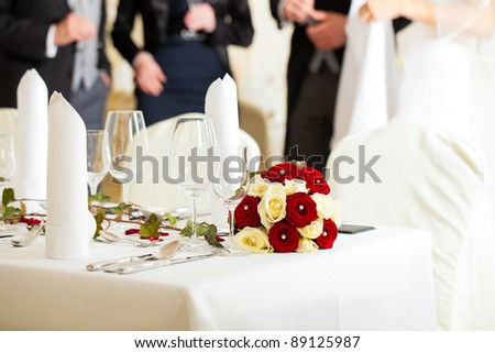 Wedding table at a wedding feast decorated with flowers - stock photo