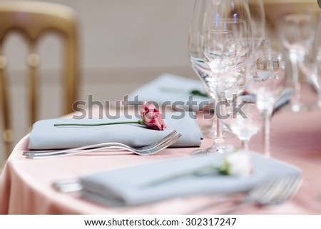 wedding table decoration. flowers, tableware, glasses, plates, cups, forks, napkins. close-up - stock photo