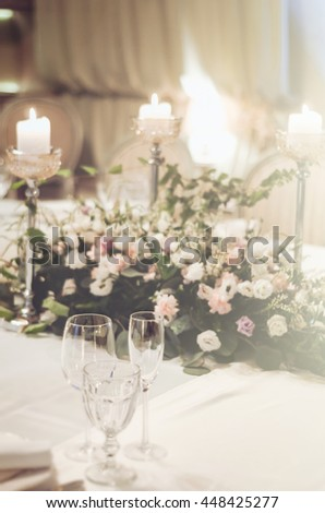 Wedding table set, elegant decoration in banquet restoraunt. Floral composition beige roses flowers with high candle coasters, glass goblets for wine. Selective focus. Luxury. Text, free copy space. - stock photo