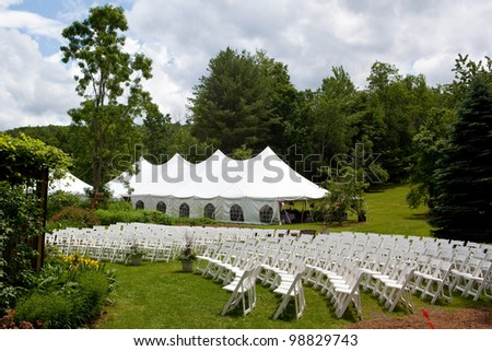Wedding tent set up for an outdoor wedding or other event. chairs set up for an outdoor ceremony - stock photo