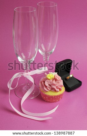 Wedding theme bridal pair of champagne flute glasses with pink cupcake and wedding ring in black jewelry box against a pink background. Vertical. - stock photo
