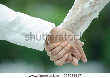 wedding theme, holding hands newlyweds - stock photo