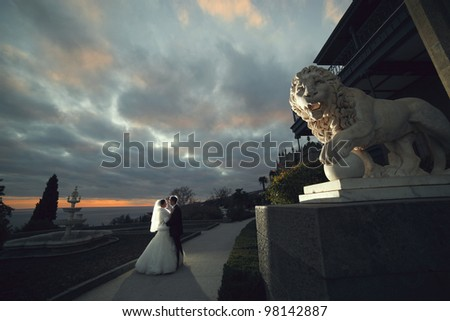wedding theme, the bride and groom embracing at sunset near the stone lion - stock photo