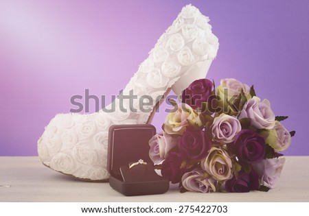 Wedding theme white floral bridal shoes with flowers on shabby chic white table and purple background, with applied retro style filters and added lens flare light beam. - stock photo