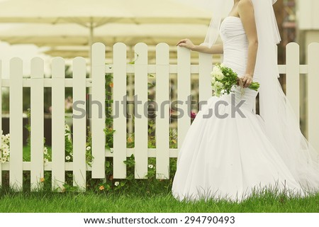 Wedding trends concept. Bride's hands with bouquet of beige flowers over white wooden fence and green lawn. Trendy dress with vapory veil. Country vintage style. Copy-space. Outdoor shot - stock photo