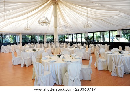 Wedding venue under a marquee with decorated tables and chairs draped in white linen around a central pole supporting the canvas - stock photo