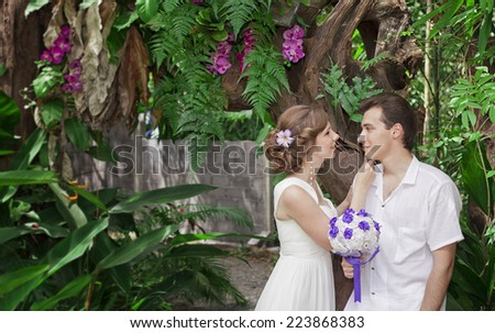 Wedding walk. The groom and the bride in Thailand, the island Samui. Tropical garden. - stock photo
