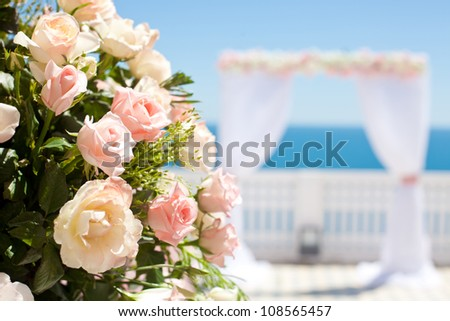 Wedding with arch and sea in background. Focus on a bouquet of roses. - stock photo