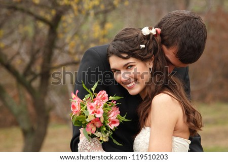 wedding, young groom kiss bride in love over autumn nature background, park fall outdoor - stock photo
