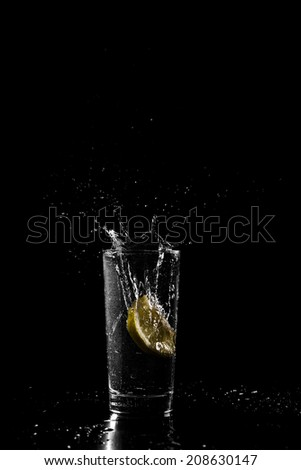 Wedge of fresh tangy lemon dropping into a cold drink of water or alcohol in a tall glass with a splash and spray of droplets against a dark background with copyspace. - stock photo