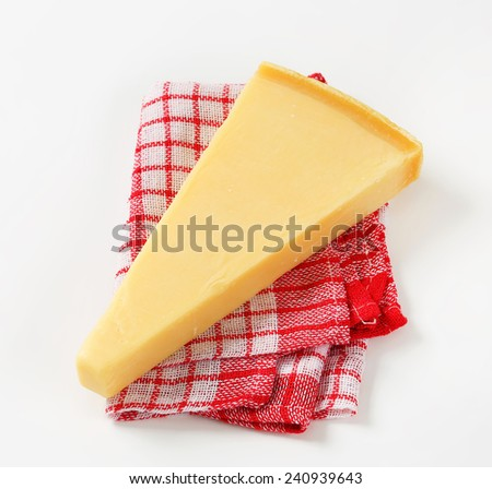 Wedge of Parmesan cheese on checked tea towel - stock photo