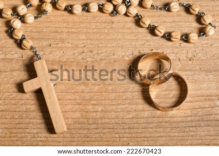 weding rings and rosary on the old wooden desk - stock photo