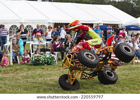 WEEDON, UK - AUGUST 28: An unnamed rider of the Kangaroo Kid quad stunt duo demonstrates how to ride an ATV on two wheels to the public at the Bucks County show on August 28, 2014 in Weedon. - stock photo