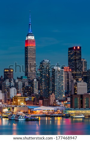 WEEHAWKEN, NJ, UNITED STATES - FEBRUARY 17, 2014: Empire State Building at dusk. The top of the iconic skyscraper displays the American flag colors, blue-white-red, in honor of Presidents' Day. - stock photo